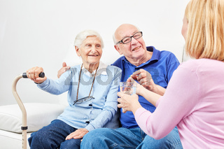 Lächelnder Senior nimmt Tablette mit Wasser ein