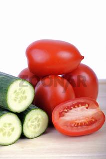gruene Salatgurken und Tomaten auf Schneidebrett