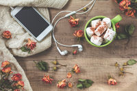 Cup of coffee with marshmallow, white knitting wool, dried roses flowers, mobile phone and headphones