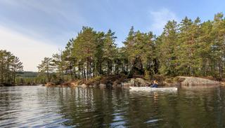 Adult senior man paddling Norwegian river in white kayak in Nidelva, Norway