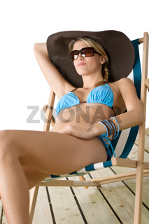 Beach - Young woman in bikini sitting on deck chair