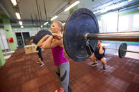 group of people training with barbells in gym