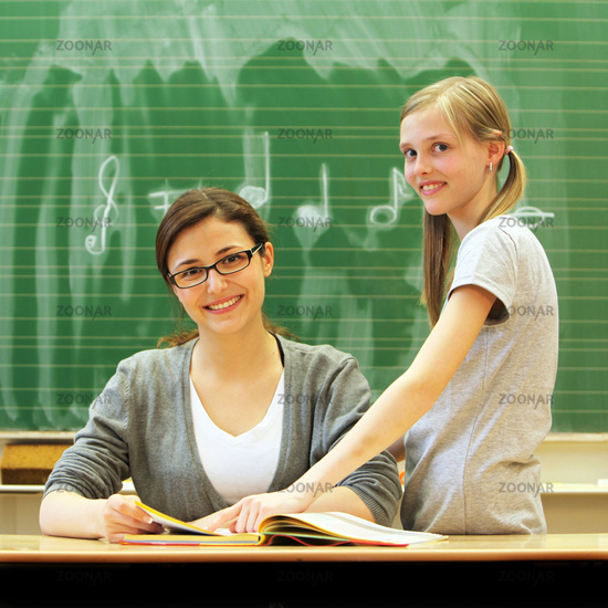 Young friendly teacher and student in the classroo