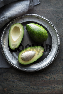 Avocado in the metal plate on the dark scratched table vertical