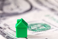 Miniature house on dollar note background