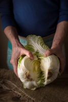Woman shares the Chinese cabbage into two halves on the table