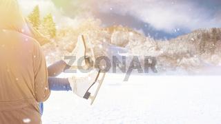 Mann trägt Frau mit Schlittschuhen im Winter