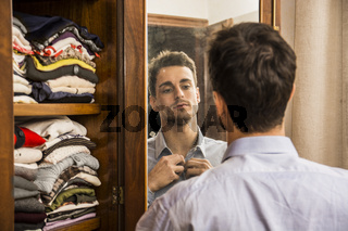 Young man standing in his bedroom dressing at mirror