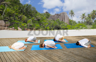 group of people making yoga exercises over beach