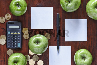 The concept: business, investment, enrichment. Green apples, gold coins, calculator and paper for entries on the office table