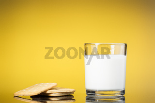 Crackers and a glass mug of milk on a yellow background