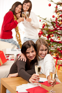Four smiling women with glass of champagne on Christmas