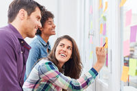 Junge Geschäftsfrau im Ideen Workshop mit Kollegen