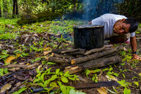 Indigenous man cooking and blowing fire on a firewood in Peruvian Amazon