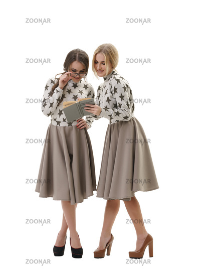 Smart young girls posing in studio with a book