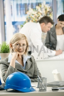 Smiling designer sitting at desk