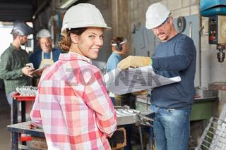 Junge Frau als Lehrling in einer Werkstatt