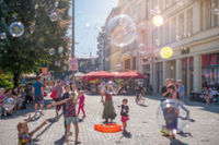blurry street scene concept , Girl making soap bubbles on a sunny day