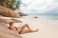 Woman reading book on picture perfect beach Anse Patates on La Digue Island, Seychelles.