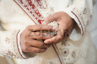 Indian groom holding ring
