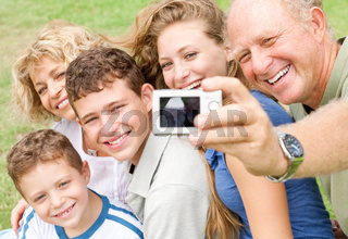 Happy family of five smiling at camera as grandfather clicks moment of the day