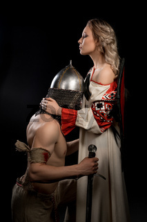 Young viking on his knees before beautiful wife