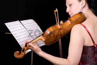 young woman plays the viola on black background