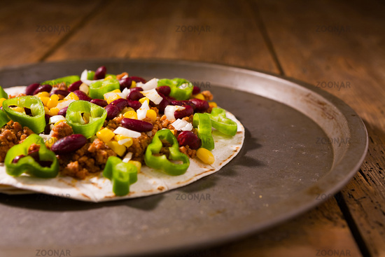 Mexican tortillas with meat, red beans, Jalapeno pepper and onion