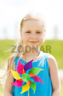 happy little girl with colorful pinwheel at summer