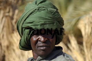 Dunkelhäutiger junger Mann mit grünem Durban