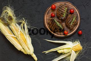 Steak grill, barbecue corn on the black background. closeup
