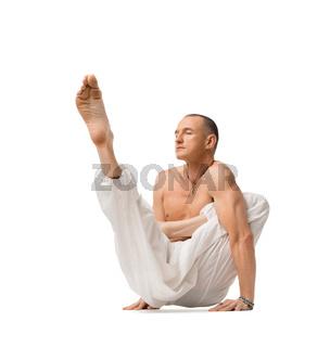 Mature shirtless muscular man practising yoga