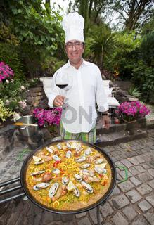 Ein Koch bereitet eiine Paella