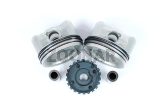 Close-up of spare parts two new pistons with connecting rods for a gasoline engine with installed sets of piston rings and crankshaft sprocket on an isolated white background