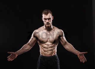 Aggressive man is a fighter, a bodybuilder with a naked torso on a black