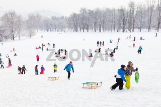 Winter fun, snow, family sledding at winter time.