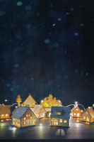 Wooden houses with lights on table for the holidays