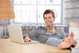 Portrait of young guy at home with computer
