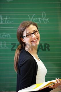 Lehrerin oder Studentin vor einer Schultafel mit Buch -