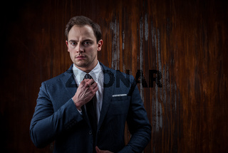 Portrait of a businessman on black wooden background