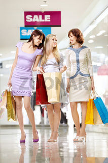 Three cheerful girl-friends with bags on walk in shop