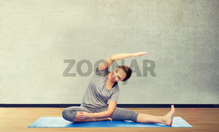 happy woman making yoga and stretching on mat