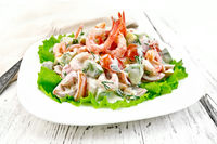 Salad with shrimp and avocado in plate on light board