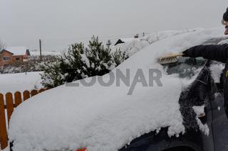 Person entfernt Schnee von eingeschneitem Auto mit Schneebesen