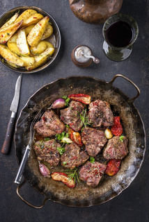 Barbecue T-bone lamb steak with fried potatoes and seasonings as top view in an iron cast pan