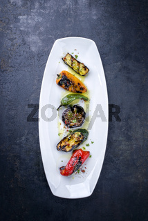 Traditional Italian barbecue antipasti creative decorated as top view on a white plate