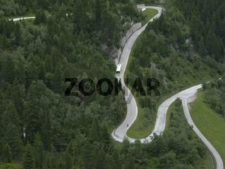 Serpentinen in den Alpen mit Bus und Bikern