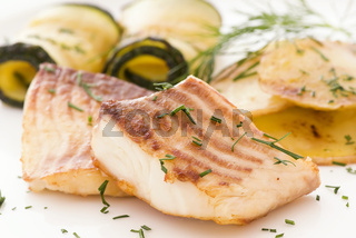 Tilapiini fillet with zucchini, potatos and leek as closep on a white plate