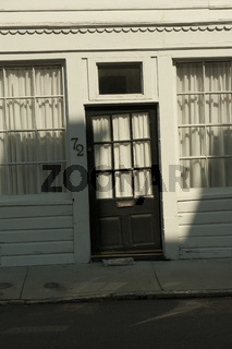 An old storefront with a black lop-sided doorway in a building in Charleston, SC.