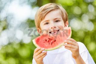 Junge auf einer Party isst eine leckere Wassermelone